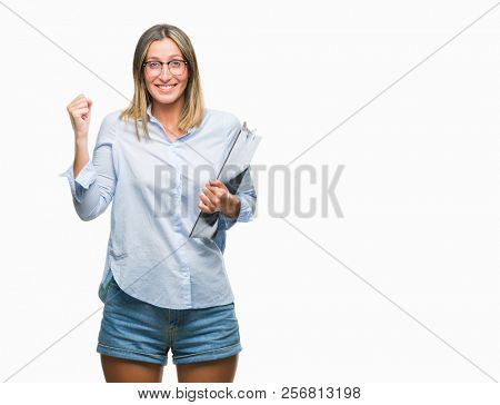 Young beautiful inspector business woman over isolated background screaming proud and celebrating victory and success very excited, cheering emotion