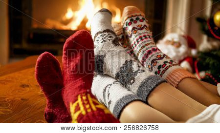 Closeup Photo Of Female Feet In Warm Woolen Socks Warming By The Fireside At House