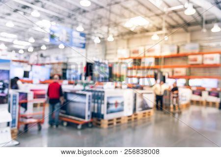 Filtered Tone Blurry Background Customer Shopping With Flatbed Cart For Big Screen Tvs