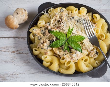 Pasta Cavatappi With Cepes In A Iron Pan On The Wood Table