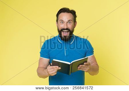 Great Idea. Handsome Inspired Mature Man Holds Notepad Looking At Camera While Standing Against Yell