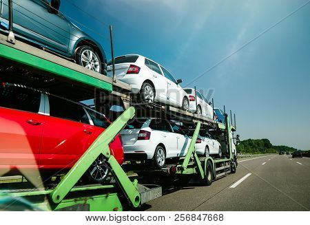 View Of Long Truck Transporting New Cars And Riding On Highway In Sunlight Under Blue Sky - Generic