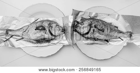 Wide image of two gilt-head bream fish on the aluminum foil on white table - view from above od delicious food homemade - back and white poster