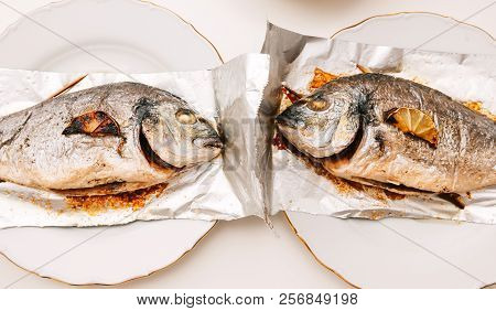 Two gilt-head bream fish on the aluminum foil on white table - view from above od delicious food homemade filter instagram style poster