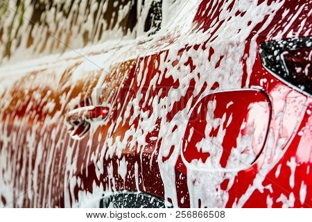 Red Compact Suv Car With Sport And Modern Design Washing With Soap. Car Covered With White Foam. Car