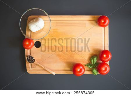 Tomatoes, Mozzarella, Pepper And Green Basil Leaves On Wooden Cutting Board On Dark Background