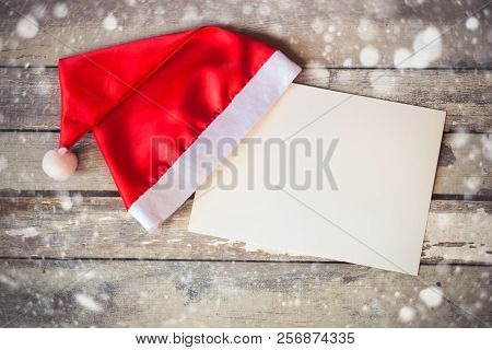 Christmas Card With Santa Hat  On Aged Wooden Background