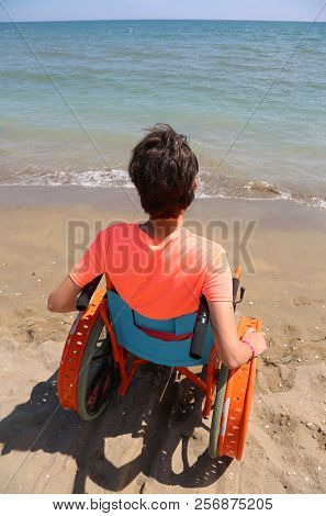 Young Boy Uses Special Wheelchair In Front Of The Sea In Summertime