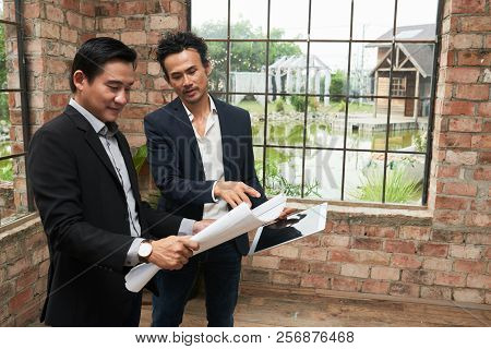 Businessman Showing Construction Plan To Investor In New Office Building