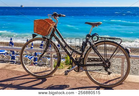 Bicycle With A Wicker Basket On Famous Promenade Des Anglais With The Mediterranean Sea In The Backg