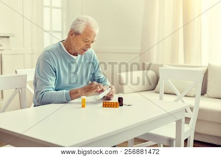 Lonely Retired Man Taking Medication Out Of Weekly Organizer