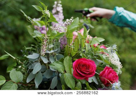 ST. PETERSBURG, RUSSIA - JULY 20, 2018: Florist of Mila Schumann Studio Flowers & Design prepares the bouquet for the festival Imperial Bouquet in the park of State Museum Pavlovsk