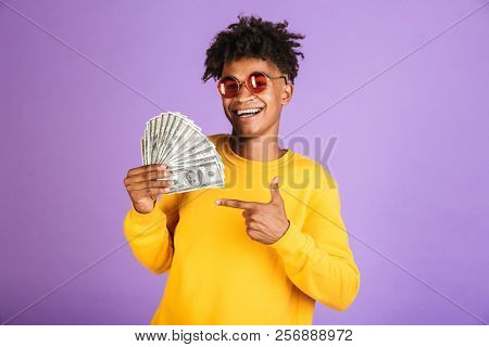 Portrait of teen african american guy wearing sunglasses smiling while holding cash money dollars isolated over violet background