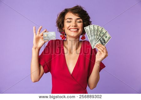 Photo of happy rich woman 20s wearing big straw hat smiling while holding credit card and fan of dollar money isolated over white background