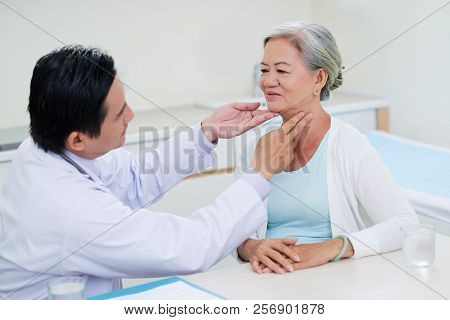 Doctor Examining Throat Of Senior Woman During Regual Check-up