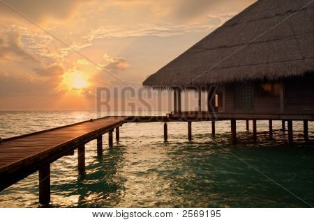 tropical beach: sunset over water. Copy space and sun beams poster