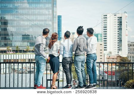Group Of Young Ambitious Vietnamese Business People Drinking Beer At Party And Looking At Big City
