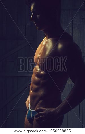 Attractive masculine sexual handsome young macho man in underpants having muscular strong breast perfect six-pack abdominal and pectoral muscles belly cool biceps side-view studio on dark background. poster
