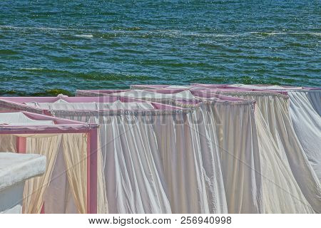 Pergolas With White Curtains Against The Background Of The Sea And Waves