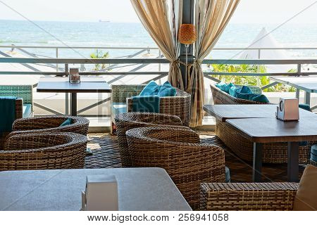 Part Of The Terrace Of The Restaurant With Tables And Chairs On The Background Of The Sea