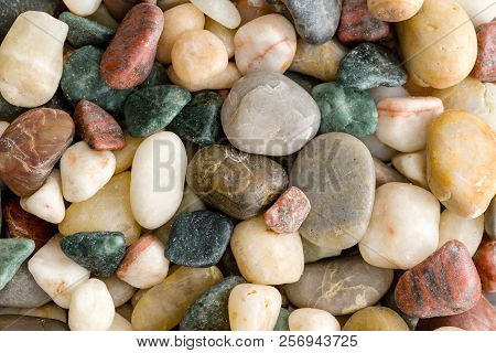 Background Texture Of Assorted Colorful Natural Smooth Waterworn Beach Pebbles, Rocks Or Stones Tumb