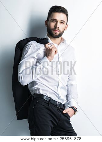 Handsome man in white shirt holds the black suit - posing  over wall. Attractive guy with fashion hairstyle.  Confident man with short beard. Adult boy with brown hair. Full portrait.