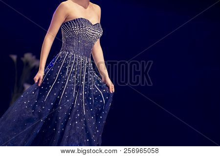 Female Model Walks The Runway In Blue Dress During A Fashion Show. Fashion Catwalk Event Showing New