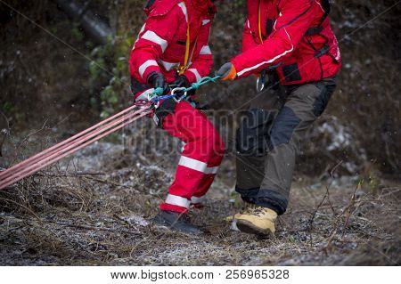 Paramedics From Mountain Rescue Service Provide First Aid During A Training For Saving A Person In A
