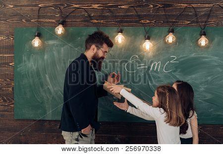 Man With Beard In Formal Suit Teaches Schoolgirls Physics. Teacher And Girls Pupils In Classroom Nea