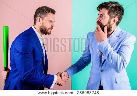 Fell Into Trap. Businessman Hides Bat Behind Back While Shaking Hands. Hidden Threat Concept. Busine
