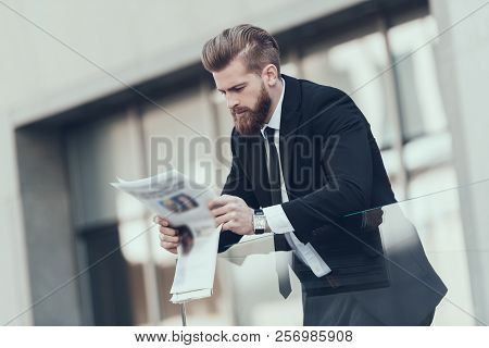 Serious Businessman Reading Newspaper Outdoor. Smiling Bearded Serious Man Wearing Suit And Glasses,