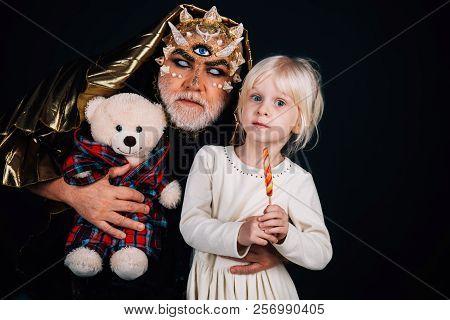 Night Monster With Child. Little Girl Child Near Man Night Monster Holding Bear. Childhood And Imagi