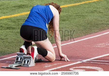 A High School Female Sprinter Is In The Starting Blocks Ready To Start Her Sprint Race On A Red Trac