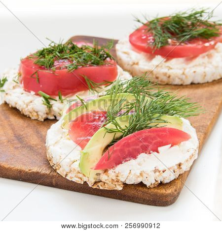Round Crisp Breads With Cheese, Tomatoes And Avocado On A Cutting Board