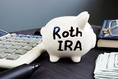 Roth IRA written on a piggy bank. Retirement plan. poster