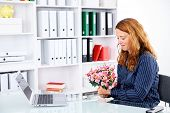 brown-haired  businesswoman in the office with big bouquet of flowers poster