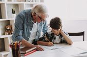 Grandson Doing School Homework with Old Man Home. Family Relationship Between Grandfather and Grandson. Grandpa Teaching, Male Grandchild, Learning Concept. Relations and People Concept. poster