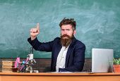 Teacher bearded man tell interesting story.Teacher interesting interlocutor as best friend. Teacher charismatic hipster sit table classroom chalkboard background. Telling educational stories poster