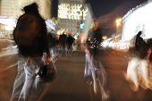People crowd walking in the city at night (blurred scene) poster