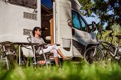 Woman resting near motorhomes in nature. Family vacation travel, holiday trip in motorhome RV, Caravan car Vacation. poster