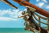 Figurehead (nose shape) is an ornament on nose of sailing vessel, rostrum or caryatid. Wooden sculpture of goddess of victory, Nick, brought happiness and luck to ancient wood sailboat Statue of luck poster