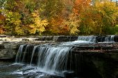 a waterfall flows in front of the fall colors. poster