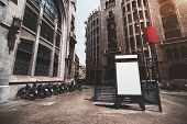 Vertical empty billboard placeholder template on the street with multiple motorbikes and subway entrance behind; blank advertising banner mockup in urban settings surrounded by historical buildings poster