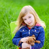 Blond kid girl with puppy pet dog sit in outdoor green grass poster