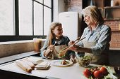 Cute Grandma and Granddaughter Cooking Salad. Grandma and Granddaughter Cooking Food. Vegetable Salad. Diet. Dieting Concept. Healthy Lifestyle. Cooking At Home. Prepare Food poster