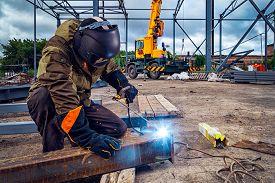 Man Welder In Welding Mask, Building Uniform And Blue Protective Gloves Brews Metal Welding Machine