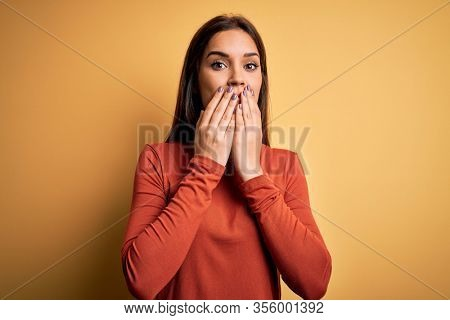 Young beautiful brunette woman wearing casual t-shirt standing over yellow background laughing and embarrassed giggle covering mouth with hands, gossip and scandal concept