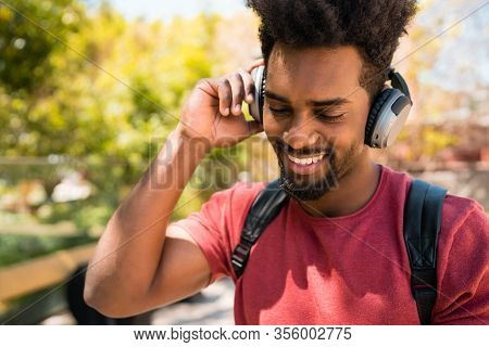 Young Afro Man Listening To Music With Headphones.