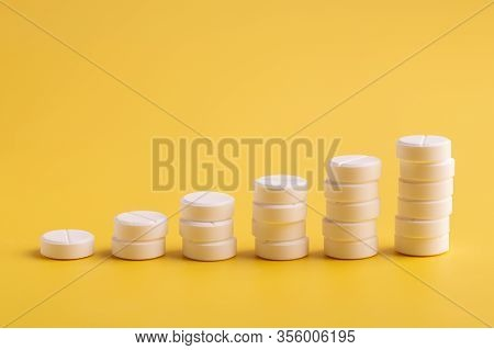 Stacks Of Pills On A Yellow Background. The Concept Of Price Increases Or Dosages. Medication Pills.