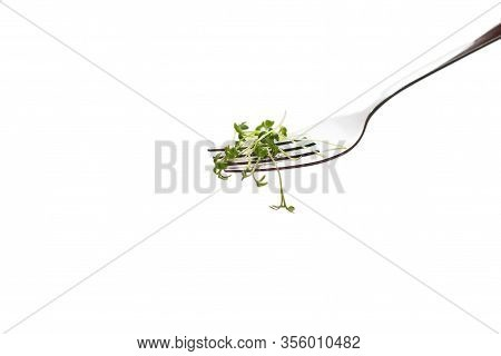 A Small Pile Of Green Watercress On A Fork And A White Background.